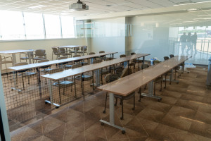 A classroom featuring long tables and chairs.