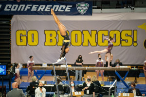Stacie Harrison swings on a bar during a gymnastics competition.