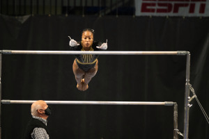 Stacie Harrison prepares to grab one of the uneven bars in a gymnastics competition.