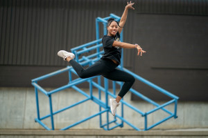 Stacie Harrison jumps for a photo in front of a sculpture outside Kohrman Hall.