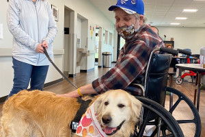 Pet Therapy handler with Sunny the dog and male participant in a wheelchair.