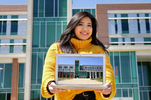A student ambassador holds up a laptop displaying a photo of Sangren Hall.