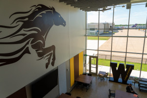 The lobby of the Aviation Education Center featuring a bronco on the wall and a W in the window.