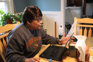 Lucinda Stinson talks while on a video call at her kitchen table.