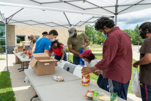 Volunteers wearing masks organize food under a tent at a collection event.