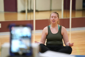 A student does yoga while livestreaming the class on Facebook.