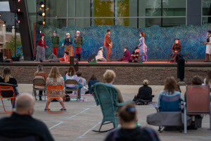 A socially distanced crowd watches actors wearing masks perform on an outdoor stage.
