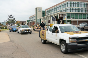 Cars decorated in Bronco gear travel around Campus Circle.