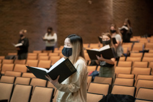 Students wearing masks sing while holding sheet music in a lecture hall.