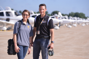 Student and flight instructor standing in front of airplane fleet