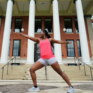A student doing yoga in front of Heritage Hall.