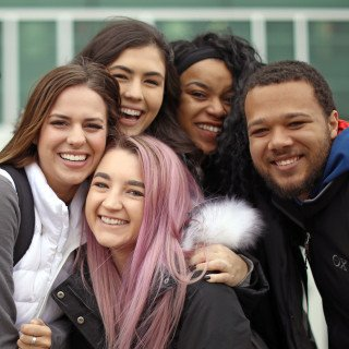 A diverse group of smiling students are gathered for a close photo