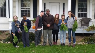A group of student volunteers standing in front of Gibbs house holding vegetables harvested from the garden.