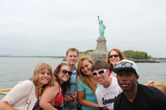 A group of honors students on a boat in front of the Statue of Liberty.