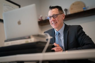 Pictured is Dr. Russell Zwanka, associate professor of marketing, sitting at a laptop.