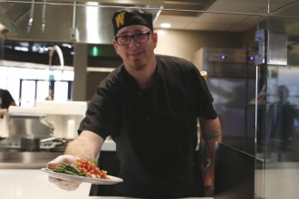 WMU Dining Services chef holding out a plate of food