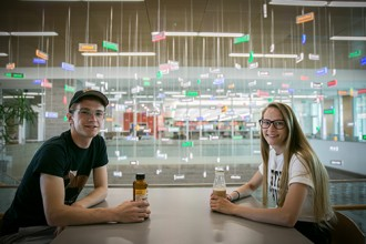 Two student sitting in front of the word art in Sangren enjoying beverages from Flossies Cafe