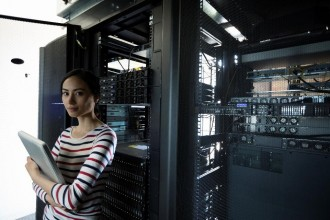 Woman in server room with laptop computer.