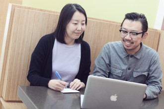 qi and qian working on a laptop