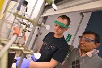 Two males wearing safety goggles conducting an experiment in a lab.