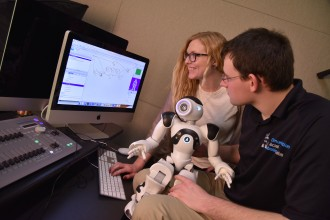 Communication students holding a robot while looking at its diagnostics on a computer screen