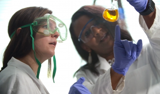 Student and faculty member wearing lab coats looking at yellow liquid in a beaker