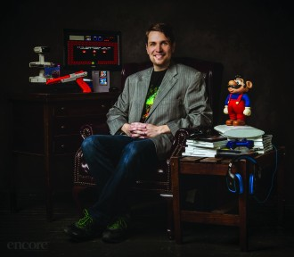Dr. Whitney DeCamp sitting with various video games surrounding him