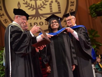 Graduate student receiving her diploma on stage