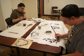 Photo of two students sitting at a table painting on a large piece of paper.