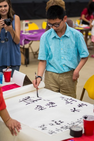 A male student practicing Chinese calligraphy on paper.