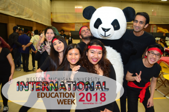 International students gathered around a large, stuffed panda bear.