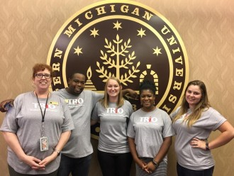 Five trio students smiling in front of the WMU logo