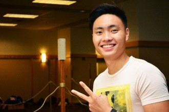 Student smiling and giving peace sign with hand