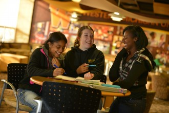 Three students sitting around a table during a study session.
