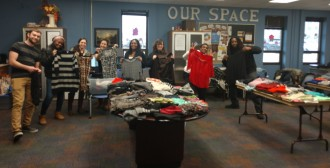 Students standing in a room holding clothes for a clothinng swap