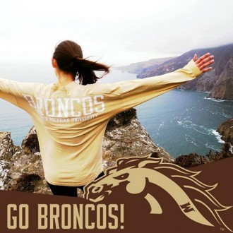 A back portrait of a female student with Bronco T-shirt who is standing on a cliff facing the ocean.