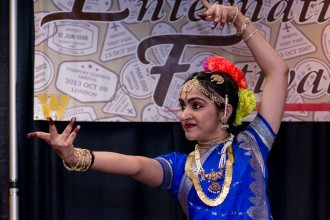 A female Indian student dancing in traditional clothes.