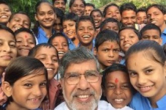 Selfie photo of Kailash Satyarthi and children laughing at the camera.