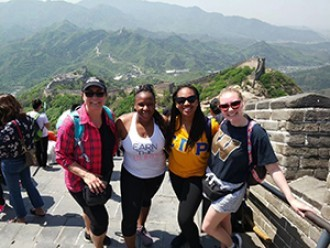 Four female students standing in front of the Great Wall of China.