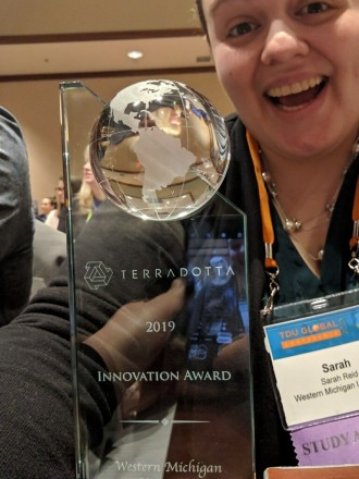 Sarah Reid smilely selfie, while holding her statue of appreciation recieved from Terra Dotta Innovation Award