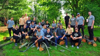 A group of hockey players sits on several trees they cut down.