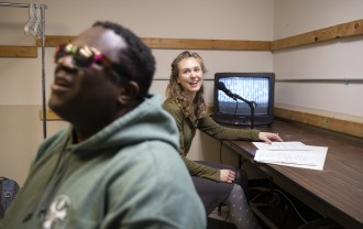 Osman Koroma listens to Abby Tongue describe what's happening during a musical performance.