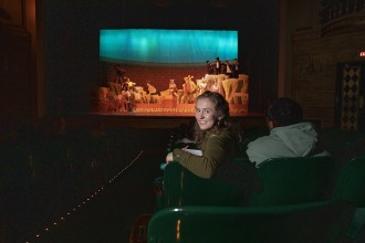 Abby Tongue sits in the theater where students are performing on stage.