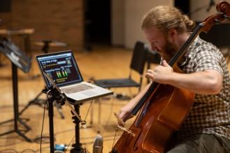 A man plays cello while looking at a computer screen.