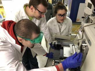 Students in lab coats analyze samples with a mass spectrometer.