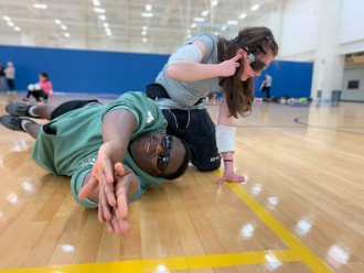 A counselor sprawls out on the floor to teach an athlete how to dive after a ball.