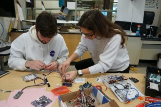 Students work on wires for a rocket.