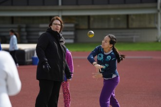 A counselor watches as a young athlete throws a shot put.