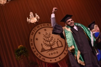 A graduate flexes his arm in accomplishment.
