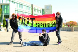 "Students hold a rainbow-colored flag that reads, ""OUTspoken."""